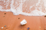 Discarded paper cup in the sand poster