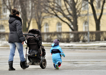 Mother with stroller walking near little son