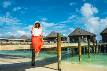 The girl on a wooden bridge near the water bungalows (Maldives -