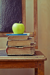 Green apple and old books on an old chair with vintage feel