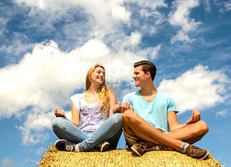 Junger Mann und junge Frau meditieren
