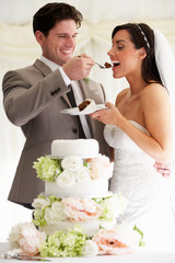 Groom Feeding Bride With Wedding Cake At Reception