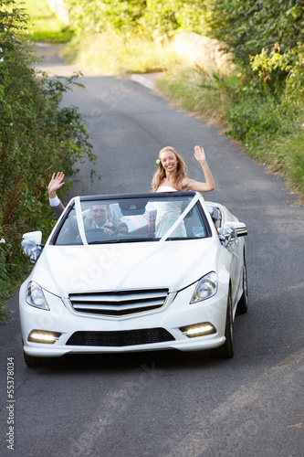 Bride And Groom Driving Away In Decorated Car