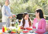 Grandparents And Granddaughter Having Outdoor Barbeque