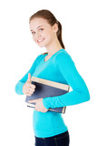 Attractive young student woman with book gesturing OK