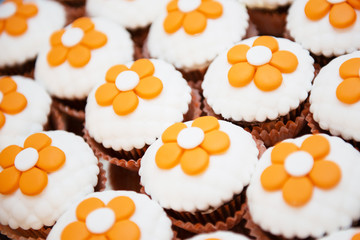 delicious chocolate cupcakes with orange flowers on top