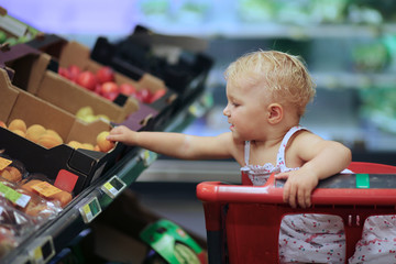 Cute baby sitting in shopping cart choosing apricot from shelf