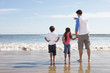 Father And Children Looking To Sea From Beach