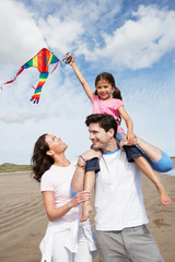 Family Having Fun Flying Kite On Beach Holiday