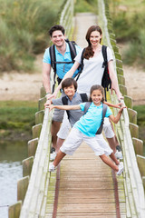 Family Walking Along Wooden Bridge