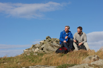 Two Men Stopping For Rest On Countryside Walk