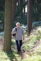 Senior Man On Country Walk Through Woodland