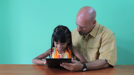 Asian Daughter Showing Dad Tricks On Digital Tablet