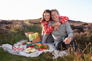 Senior Couple Having Picnic On Countryside Walk