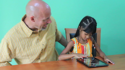 Father Helps Daughter Use Digital Tablet