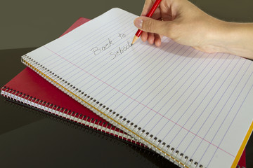 teacher writing back to school in notebook