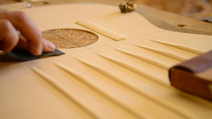 Luthier Sanding a guitar structure, close up