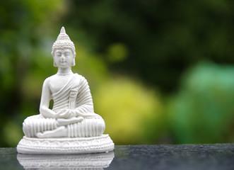 Weiße Buddhafigur im Lotussitz beim Fingermudra