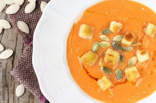 Traditional homemade pureed pumpkin soup with seeds and croutons