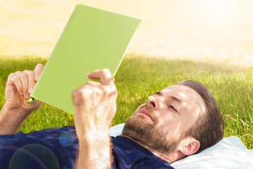 Man reading a book outdoor while laying on grass