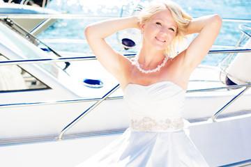 Beautiful bride posing near the sea and yachts
