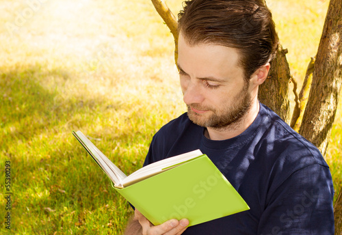 Man reading a book outdoor in the garden