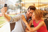 Happy young couple taking selfie in cafe poster