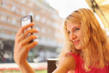 Young woman taking selfie on cell phone poster