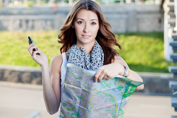 young woman tourist holding paper map