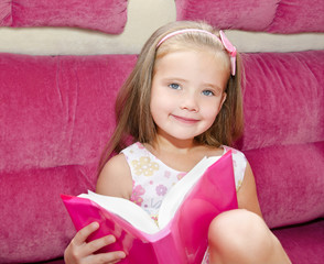 Little girl reading a book and siting on the sofa