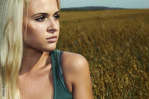 sad beautiful blond woman on the field.nature background