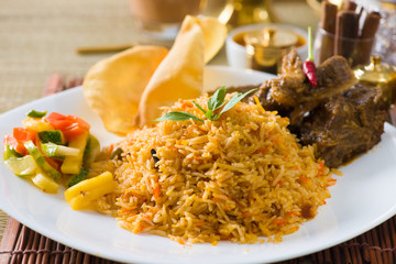 Biryani mutton rice papadam with traditional background