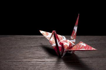 暗い木目に赤色の折り鶴のアップ