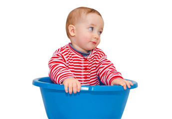 Cute baby dressed and sit in a blue basin