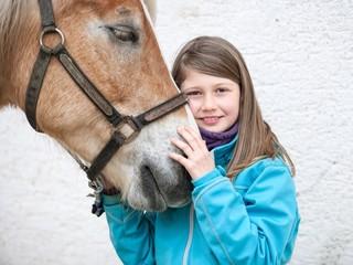 Kind streichelt Pferdekopf