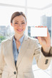 Smiling businesswoman holding up blank business card