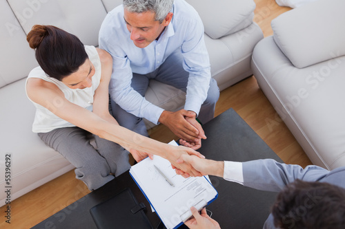 Businesswoman doing handshake with a businessman sitting on sofa