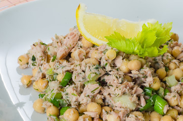 Close up on a dish of chickpea salad with tuna and herbs