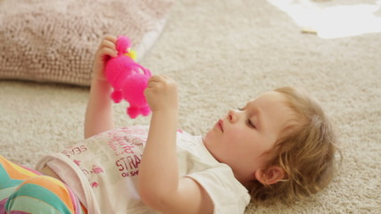 Little girl is playing with toy while laying on floor