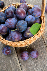 plums in basket on wooden surface