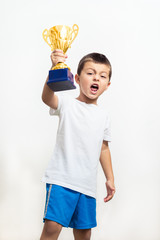 Little boy celebrates his golden trophy