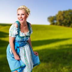 junge blonde Frau im Dirndl vor ländlichem Hintergrund