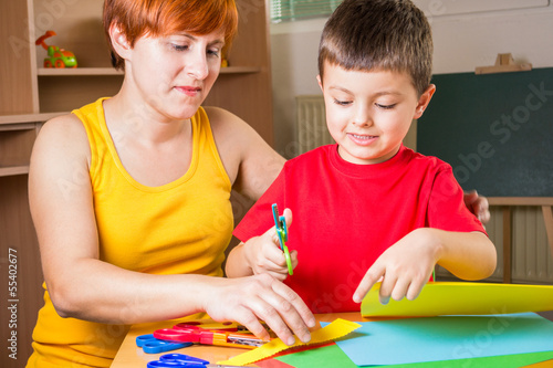 Mother cuts paper with his son