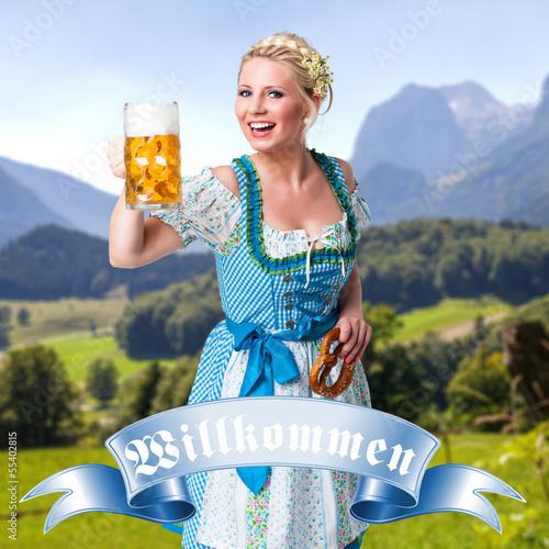 junge blonde Frau im Dirndl vor Alpenpanorama