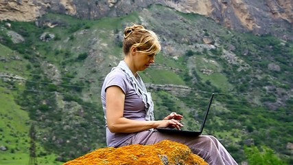 A woman is sitting on a huge rock and prints on the laptop