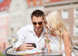 couple looking at smartphone in cafe