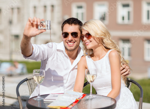 couple taking photo in cafe