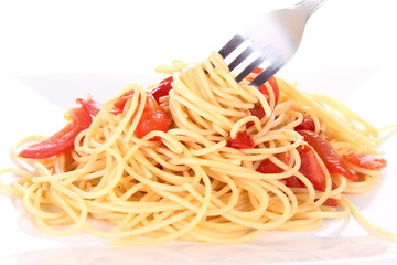 Pasta with tomatoes and garlic being eaten with a fork