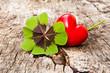 vierblättriges Kleeblatt und rote Herz auf Holz