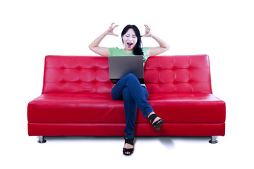 Angry female sitting on red sofa - isolated